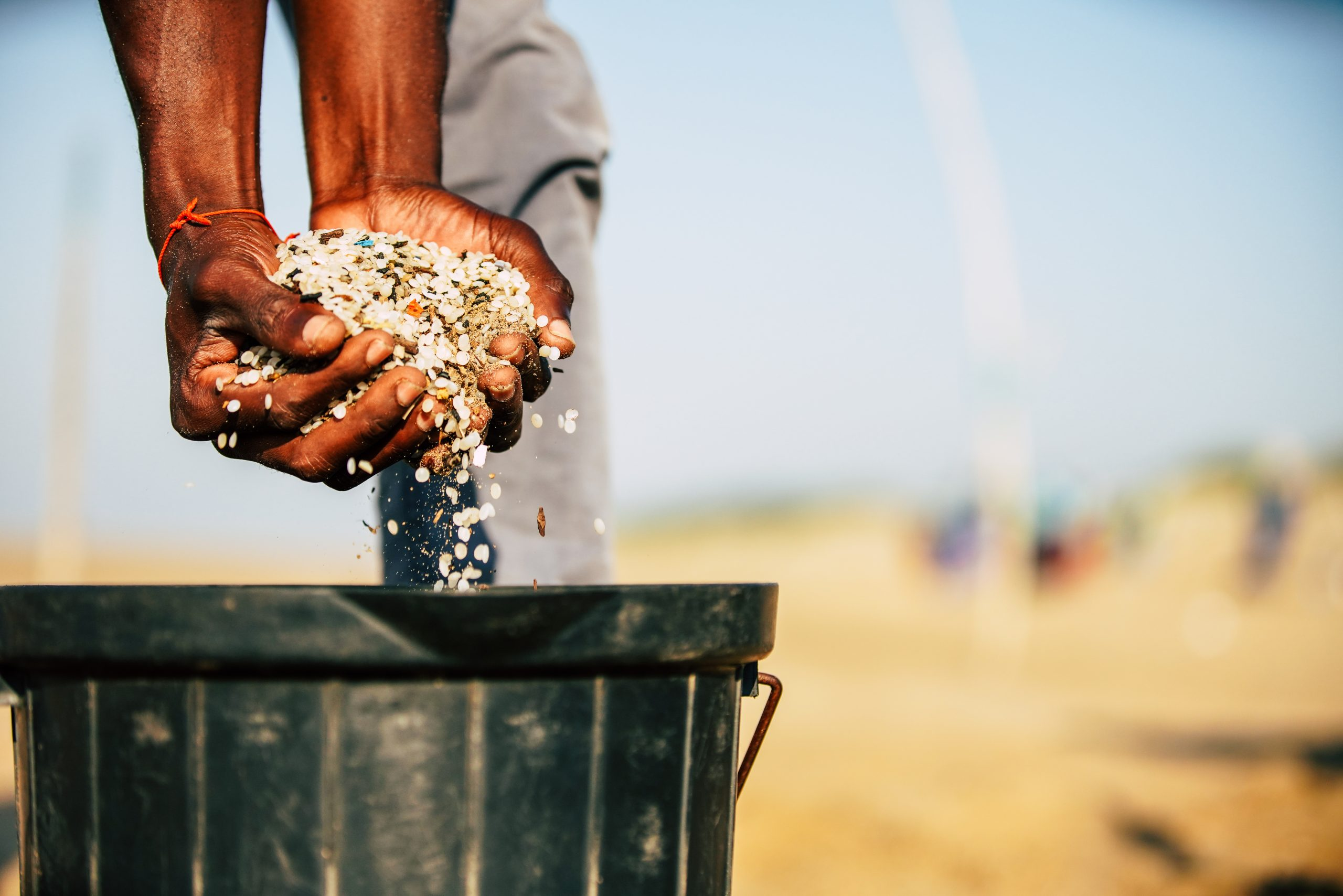 Hands holding plastic pellets on beach in Africa
