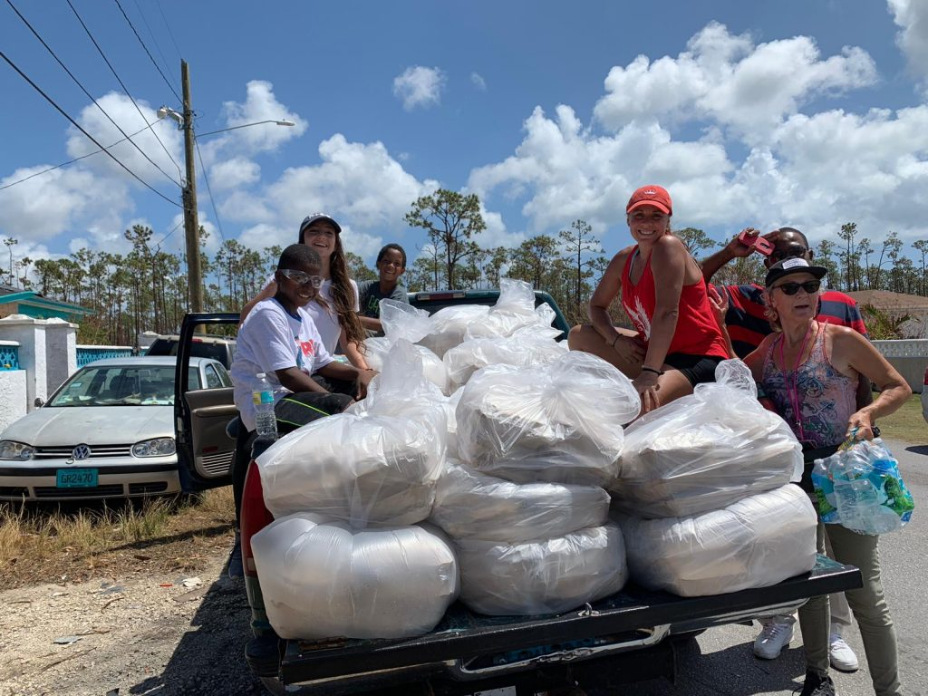 Volunteers on the back of pickup truck with supplies